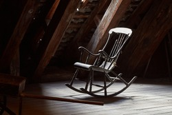 Old rocking chair on a dim attic window light