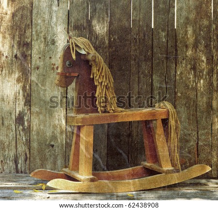 Old rocking horse in the partial shade on a rustic country backdrop.  Grunge textured.