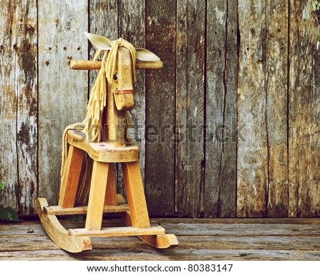 Old rocking horse on a rustic country backdrop.