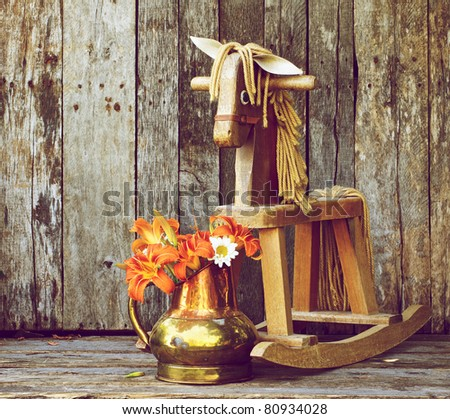 Old rocking horse  with orange lilies and daisies in an antique copper vase on a rustic wood backdrop.