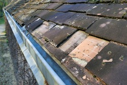 Old roof in a state of disrepair with broken tiles falling into the gutter