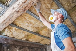 Old Roof Insulation. Caucasian Construction Worker in His 30s Inspecting Aged Roof and Mineral Wool Insulator.