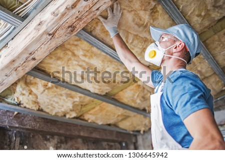 Old Roof Insulation. Caucasian Construction Worker in His 30s Inspecting Aged Roof and Mineral Wool Insulator. Photo stock ©