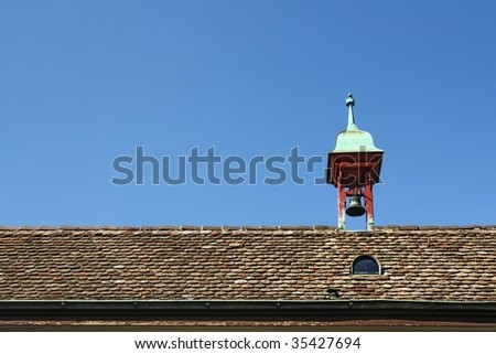 Old Roof with Small Bell Tower against blue sky
