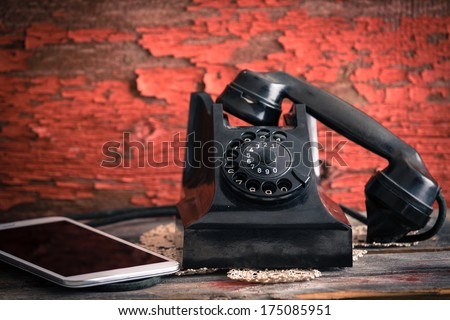 Old rotary telephone with its receiver off the hook alongside a tablet computer showing the old-fashioned and modern forms of communication against a grungy wooden wall with peeling paint
