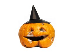 Old rotten and angry orange pumpkin lantern jack in a black witch hat. Jack-o-latern isolated against background. End Halloween celebrations, memory
