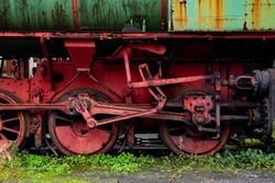 Old rotten, rusty steam engine of  railway locomotive with metal details of the machinery, screws, leaf suspension pipes, wheels, cylinders, linkage struts. Peeled off and corroded red and green color