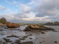 Old, rotting boats, wrecks on the mud flats. River Torridge Estuary near Appledore in north Devon, England, UK.