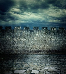 Old rough brick wall background texture. Ancient medieval wall and tiled floor with dramatic cloudscape