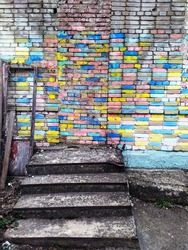 Old rough stairs with colorfull brick wall on the background