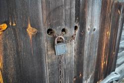 Old rough vintage chain with a padlock locking the old animal shed door. Wooden big door with an old school door locking mechanism. Grunge looking door with its old locking system. Wooden construction