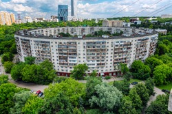Old round residential building in Moscow in greenery. Summer, sunny day.