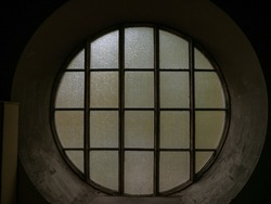 Old round window with interesting architecture in a dark room, low light and creepy atmosphere