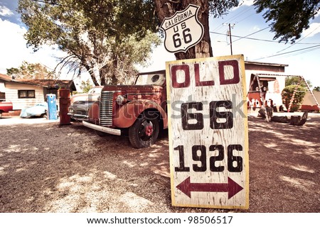 Old route 66 signs with rusty cars in background