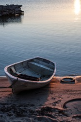 Old rowboat pulled to the shore in the morning while the sun is shining and the water is still.