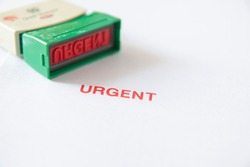 Old rubber stamp, used office equipment, then put on white paper  and a red URGENT message, earning money and urgently needing money, or working to make money urgently.