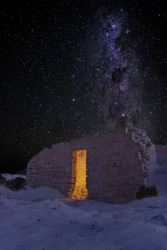 Old ruin in the desert at night with the milky way full of stars, magical atmosphere
