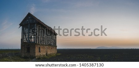 Old ruined abandoned barn in a farm field at sunrise #1405387130