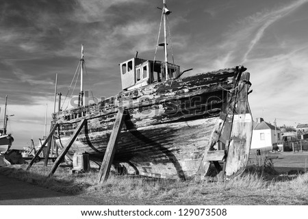 Old ruined boat at Burghead harbour, Scotland, awaiting restoration. - stock photo