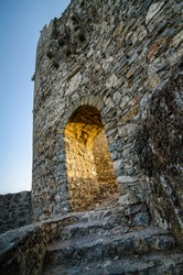 Old ruined castle at sunset with a staircase and an arch illuminated by sunlight