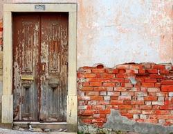 Old ruined door in brick wall background