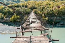 Old ruined foot bridge over the Vjose in Permet Albania. photographed in perspective