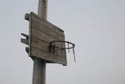 Old ruined ghetto style basketball hoop. Basketball ring with chains against grey sky with copy space.