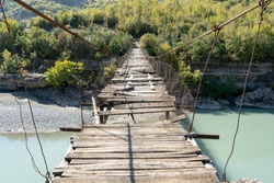 Old ruined wooden hanging bridge in over Vjosa river in Albania. Scary place to walk through since the whole thing its broken