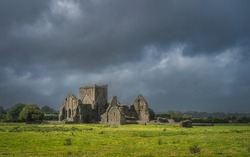 Old ruins of Hore Abbey illuminated by sunlight with dark dramatic storm sky. Located next to Rock of Cashel castle, County Tipperary, Ireland
