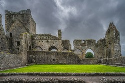 Old ruins of Hore Abbey with remaining arches and walls, dramatic storm sky. Located next to Rock of Cashel castle, County Tipperary, Ireland