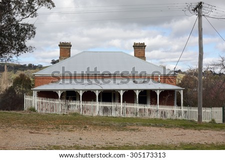 Old run down Australian house with corrugated iron roof, verandah with fancywork and  white picket fence in rural countryside scene.  A bygone era.
