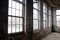 Old rundown warehouse with lots of windows.