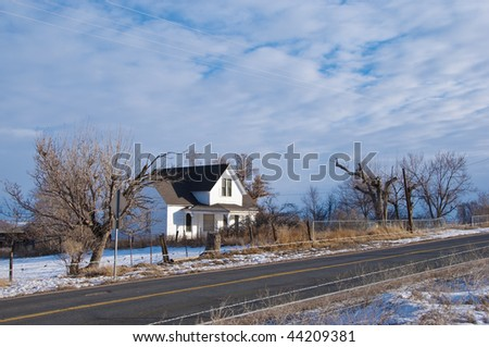 Old rural farm house by a small road with old trees and snow in winter, in the Colorado prairie