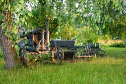 Old rural tractor and field plowing equipment