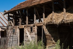 Old rural wooden barn with dry hay. Farm scene with traditional barn. Place for animal feed storage on a farm. Life in the countryside
