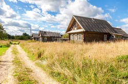 Old rural wooden houses in abandoned russian village in summer sunny day. Novgorod region, Russia