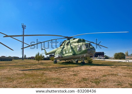 old Russian helicopter on the grass. Against the background of blue sky.
