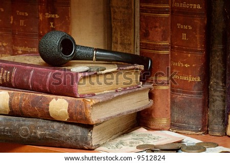 Old Russian imperial books smoking pipe and coins horizontal - stock photo