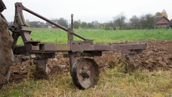 Old Russian metal plough on metal wheels plowing the brown field furrow close up front side view, soil cultivation at autumn day on rural background, countryside agriculture farming machinery