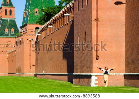 Old Russian outstanding memorial - fortified wall with towers from red brick, detail of Kremlin fortress in Moscow . And small figure of woman standing by the wall.