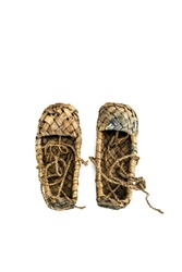 Old Russian sandals made of bark on a white background.bast shoes