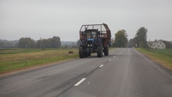 Old Russian wheeled tractor with empty hay trailer move on the rural empty asphalt road on field at autumn day for loading, front view, agribusiness farming equipment