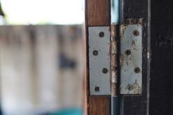 Old rust door hinges on wooden door, blurry background.