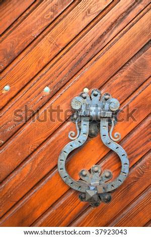Old rust door knocker on a peeling paint wood door. HDRI image - stock photo