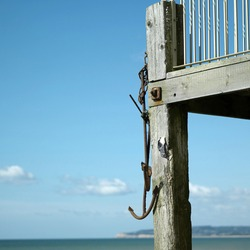 Old rusted anchor hanging on a lifeguard tower. Conceptual image