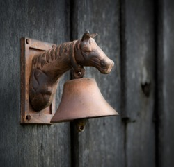 Old rusted bell on side of abandoned wooden shed