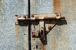 Old rusted grungy metal garage door with latch and hasp. Close up of rusty vintage lock on closed door