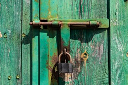 Old rusted grungy wooden garage door with latch and padlock. Close up of rusty vintage lock on closed door