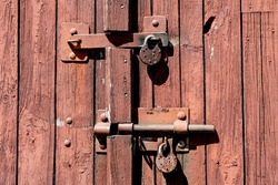 Old rusted grungy wooden garage door with latch and padlock. Close up of rusty vintage lock on closed wooden door