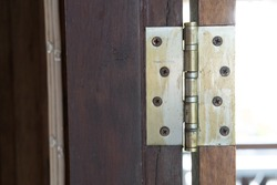 Old rusted hinge holding wooden door